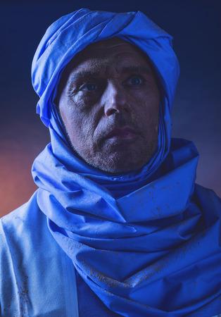 white robe: Berber man in night light wearing blue turban with white robe. Studio shot.