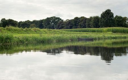 Dutch river de Berkel with small boat corn field. Achterhoek. Gelderland. The Netherlands.