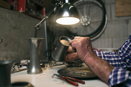 antique vase: Hands of senior man inspecting antique tin vase
