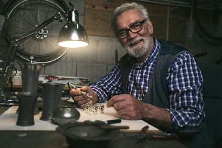 Smiling senior man soldering metal rings