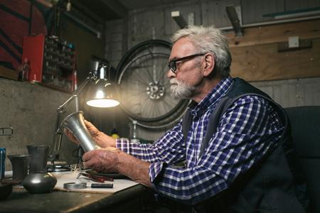antique vase: Senior man looking at antique tin vase.