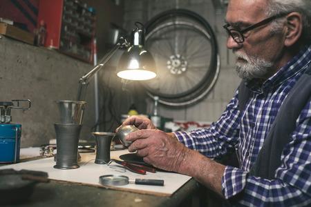 antique vase: Senior man looking at bottom of antique tin vase.