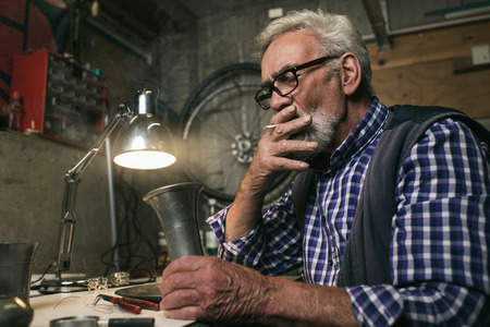 work worker: Smoking senior man inspecting antique tin vase. Stock Photo