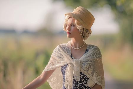 Mujer de moda de la década de 1930 con sombrero en el paisaje de verano rural.