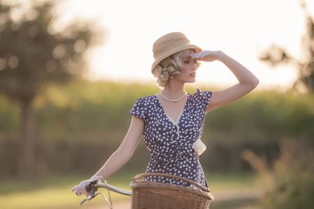 vestidos antiguos: Vintage 1930s fashion woman in blue summer dress standing with bicycle in rural landscape. Foto de archivo