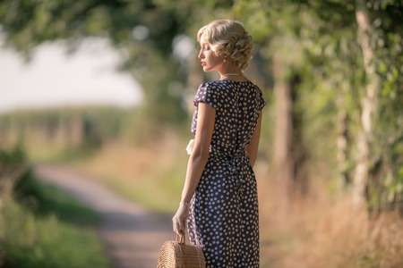 1930s vintage fashion woman standing with handbag on rural pathway. Stock Photo