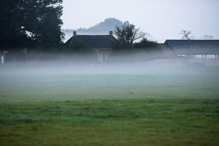 typically dutch: Old dutch farm in morning mist. Stock Photo