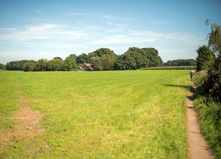 Woman cycling on small path in rural dutch landscape. Winterswijk. Achterhoek. Gelderland. The Netherlands. Reklamní fotografie