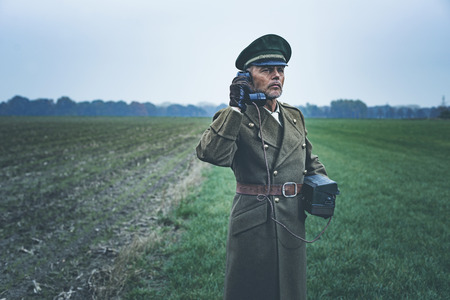 world war ii: Vintage 1940s military officer calling with field phone while standing on farmland. Stock Photo