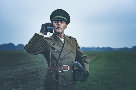 Vintage 1940s military officer calling with field phone while standing on farmland. Stock Photo