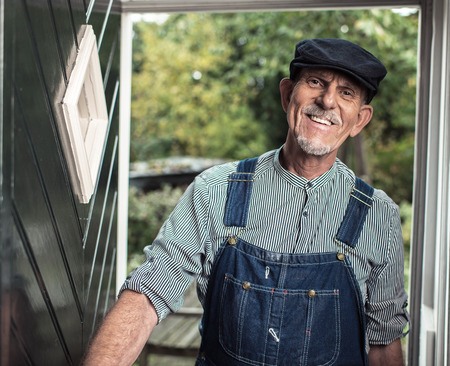 dungarees: Vintage smiling senior farmer wearing dungarees and cap entering front door of farm.