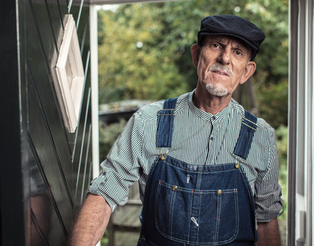 Vintage senior farmer wearing dungarees and cap entering front door of farm. Stock Photo