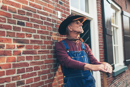 dungarees: Senior farmer in dungarees with hat standing against wall of farm. Stock Photo