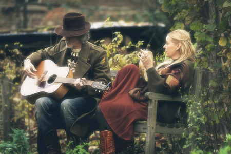 Man and woman making music on bench in autumn garden. Stock Photo