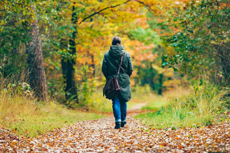 shoulder bag: Woman with shoulder bag walking on path in autumn forest. Stock Photo