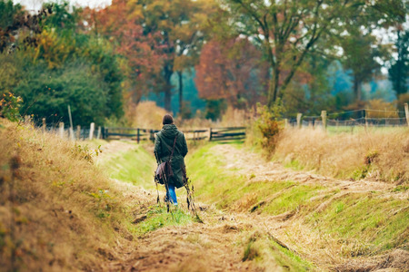 shoulder bag: Woman with shoulder bag walking in field with autumn trees.