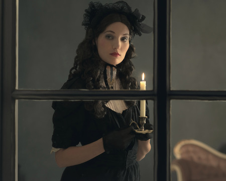 voyeur: Retro victorian woman in black dress standing behind window holding candlestick. Stock Photo