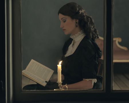victorian girl: Retro victorian girl reading book by candlelight behind window.