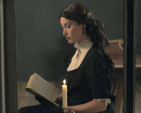 Retro victorian girl reading book by candlelight behind window.