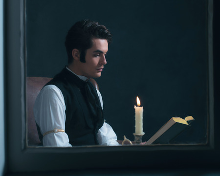scrooge: Retro victorian man reading book by candlelight sitting by window.