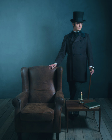 dickens: Retro dickens style man standing with cane next to leather chair. Stock Photo