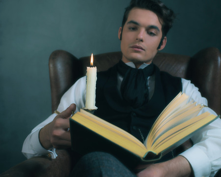 Retro victorian dickens style man reading book by candlelight. Stock Photo