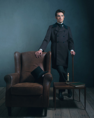 Retro dickens style man standing with cane next to leather chair. Stock Photo