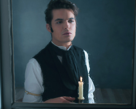 Retro dickens style man with candlestick looking out rainy window.