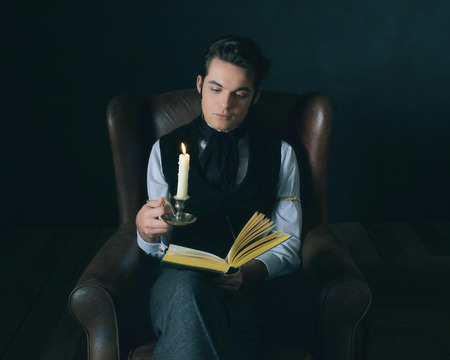 dickens: Retro victorian dickens style man reading book by candlelight. Stock Photo