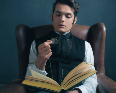 Vintage victorian dickens style man reading book with magnifying glass.