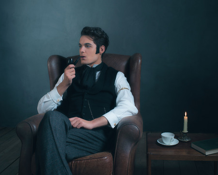 Retro dickens style man smoking pipe. Sitting in leather chair.