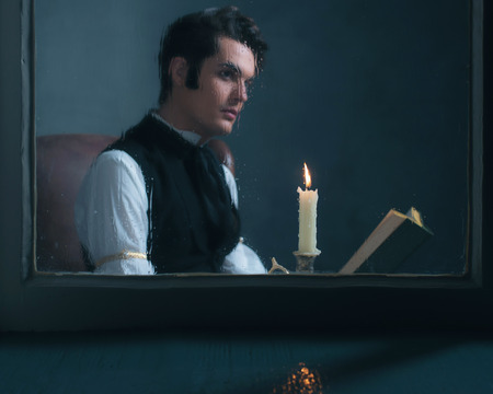 scrooge: Candlelight behind rainy window with retro victorian man reading book out of focus. Stock Photo