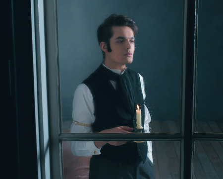 dickens: Retro dickens style man with candlestick looking out rainy window.