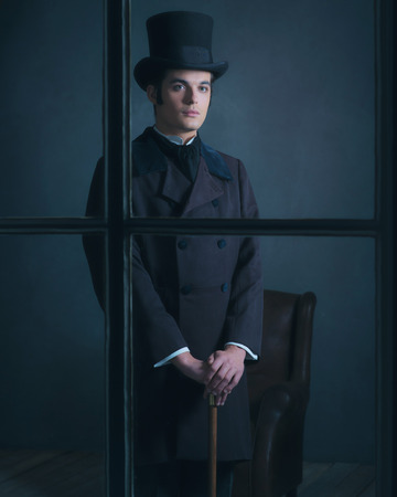dickens: Dickens style man standing with cane behind window. Stock Photo