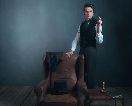 Vintage victorian man standing next to chair smoking cigarette.