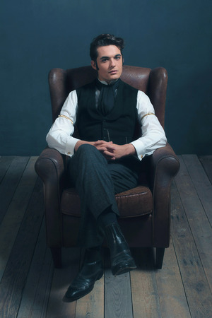 dickens: Retro victorian dickens man sitting on leather chair in living room.