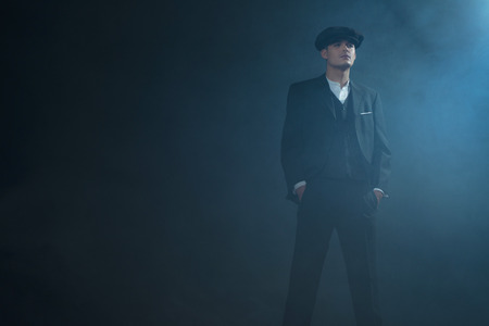 blinders: Retro 1920s english gangster wearing suit and flat cap standing in smoky room. Peaky blinders style.