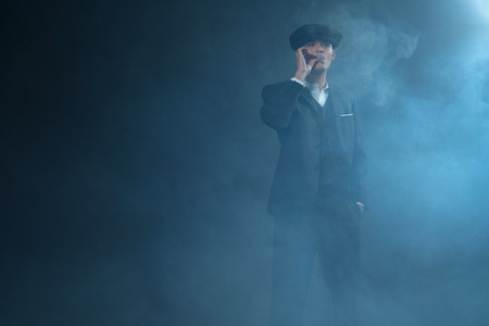distinctive: Retro 1920s english gangster wearing suit and flat cap standing in smoky room. Smoking cigarette. Peaky blinders style.