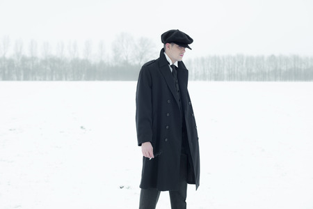 blinders: Retro 1920s english gangster with black coat and flat cap standing in winter snow landscape. Peaky blinders style.