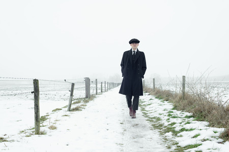 Retro 1920s english gangster with black coat and flat cap walking in winter snow landscape. Peaky blinders style. Stock Photo