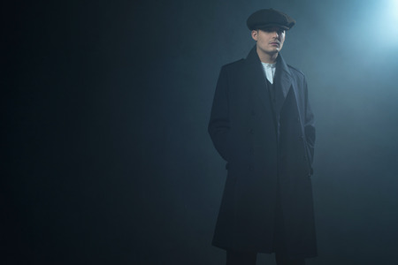 blinders: Retro 1920s english gangster wearing coat and flat cap standing in smoky room. Peaky blinders style.