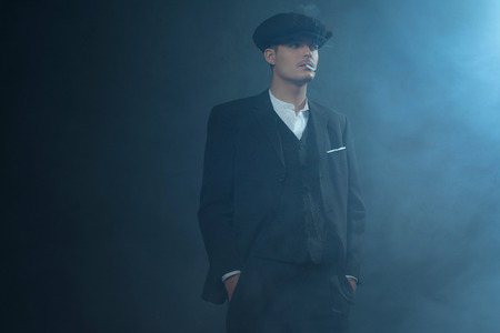 blinders: Retro 1920s english gangster wearing suit and flat cap standing in smoky room. Smoking cigarette. Peaky blinders style.