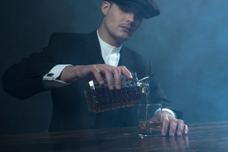 blinders: Retro 1920s english gangster with flat cap pouring whiskey. Peaky blinders style.