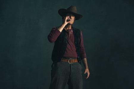 actor: Retro late 1960s spaghetti western actor. Smoking cigarette.