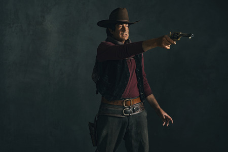 actor: Vintage late 1960s spaghetti western actor. Shooting with revolver.