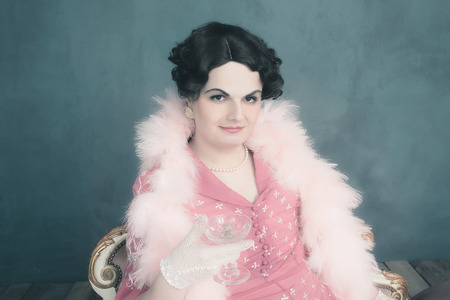 trans gender: Transgender woman vintage 1920s fashion sitting on sofa holding champagne glass.