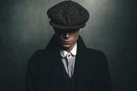 Mysterious portrait of retro 1920s english gangster with flat cap. Foto de archivo