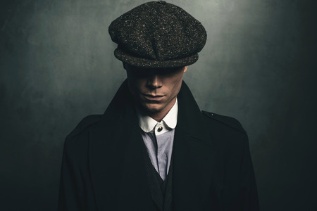 Mysterious portrait of retro 1920s english gangster with flat cap. Archivio Fotografico