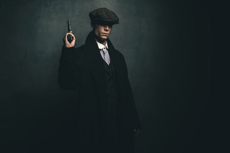 distinctive: Dangerous retro 1920s english gangster standing with gun. Stock Photo