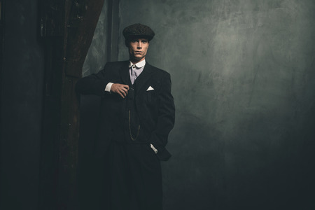 blinders: Retro 1920s english gangster wearing suit and flat cap.
